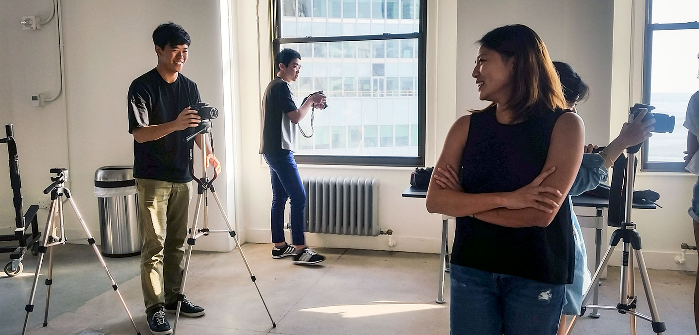three students with cameras in studio, one student posing for one of the photography students