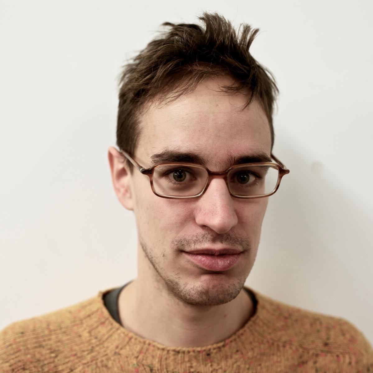 headshot of a man in a brown sweater with glasses