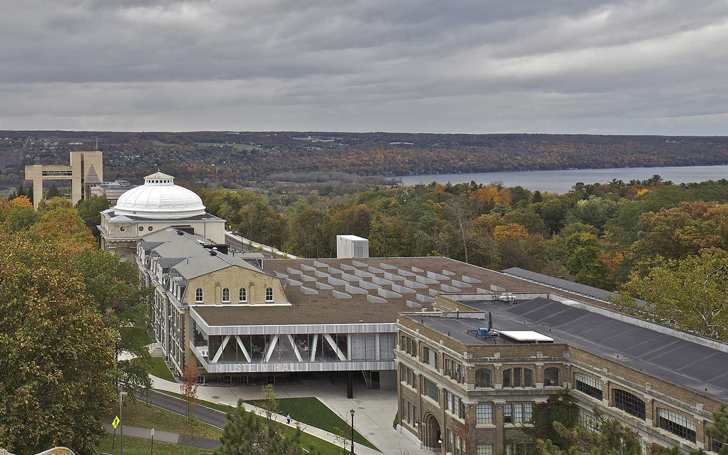 Aerial view of AAP shows Rand, Milstein, Sibley, and Tjaden halls, and includes the Herbert F. Johnson Museum of Art and Cayuga Lake in the background.