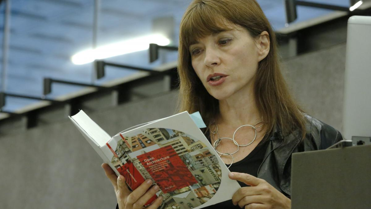 Woman holding a book and reading aloud.