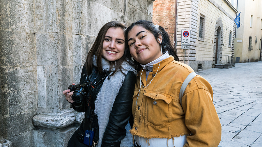 Two young women in front of an ancient wall in an Italian city