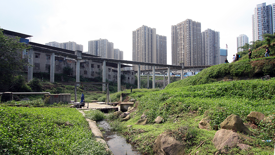High rise housing towers behind a raised viaduct and green space below
