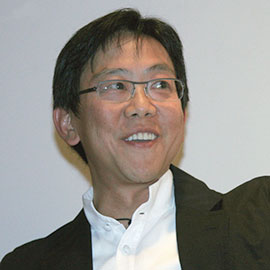 headshot of a man with black hair and glasses smiling at someone off camera