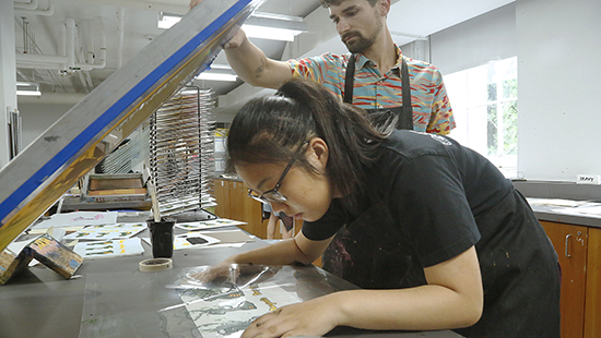 woman working with a screen printing press while instructor looks on