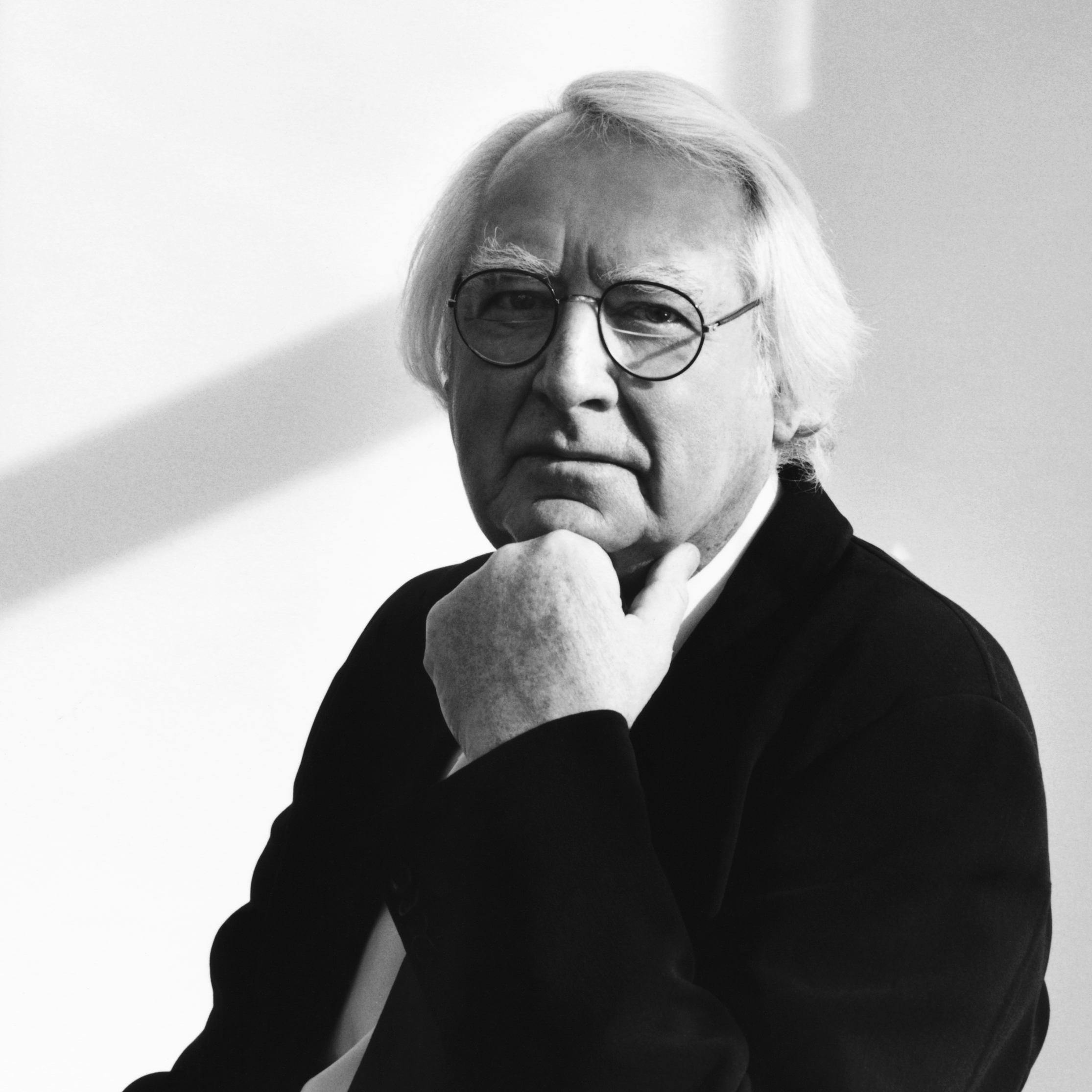 black and white image of a man with white hair and glasses, wearing a black jacket