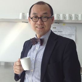 Man with short dark hair and glasses wearing a suit jacket and bowtie, holding a white mug in one hand and standing in front of shelf with more mugs