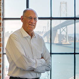 older man wearing glasses, standing in front of a window with bridge visible outside