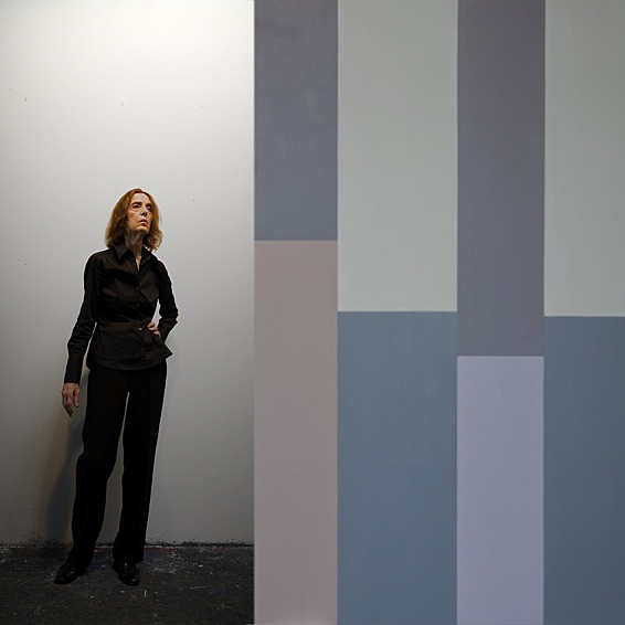 woman wearing black standing next to a painting of vertical color blocks of different shades of purple
