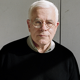 older man with white hair and glasses wearing a black sweater