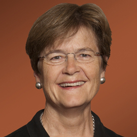 headshot of a woman with short hair and an orange background