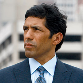 headshot of a man wearing a blue suit looking into the distance