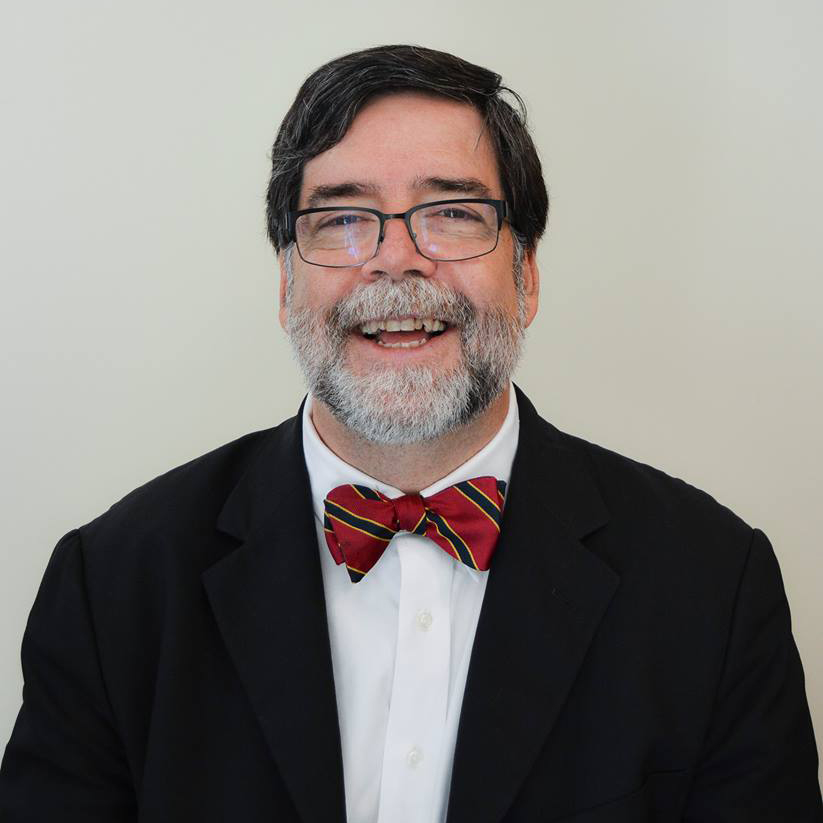 headshot of a man with a beard and glasses wearing a bowtie