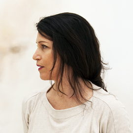 profile headshot of a woman with long dark hair wearing a white shirt