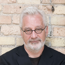headshot of a man with white hair and a beard and glasses