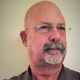 headshot of a bald man with a goatee and glasses