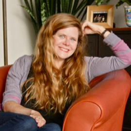 woman with long red hair sitting on a red couch