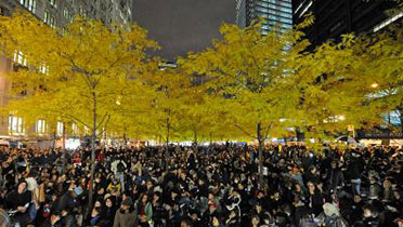 Crowds in a city in front of fall trees