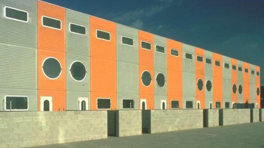 Three story row housing in gray and orange sections with round and ovoid windows