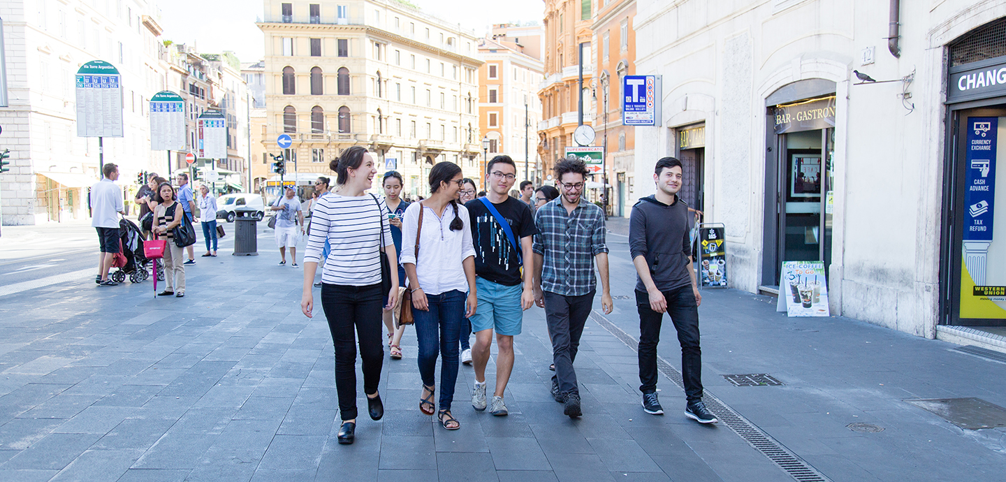 five students walking down a cobblestone street in Rome