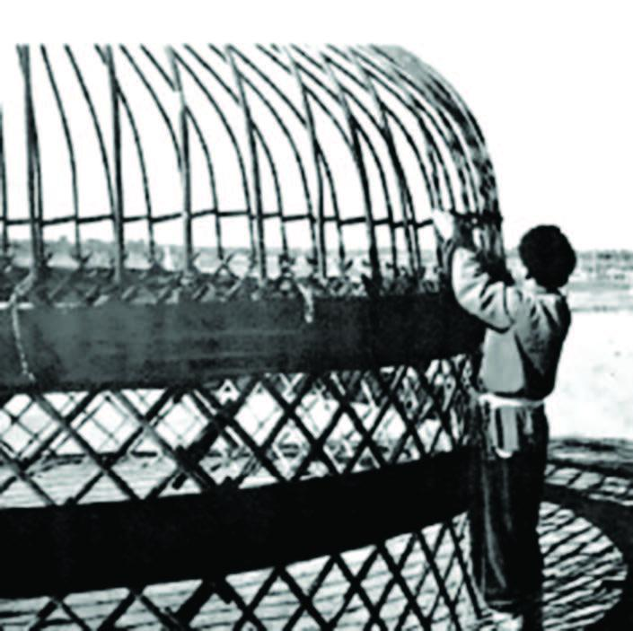 A person weaving a large domed structure.