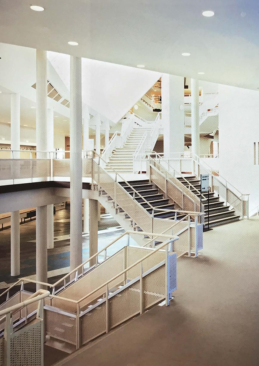 A series of stairs running between three levels with a parking lot below and an auditorium above