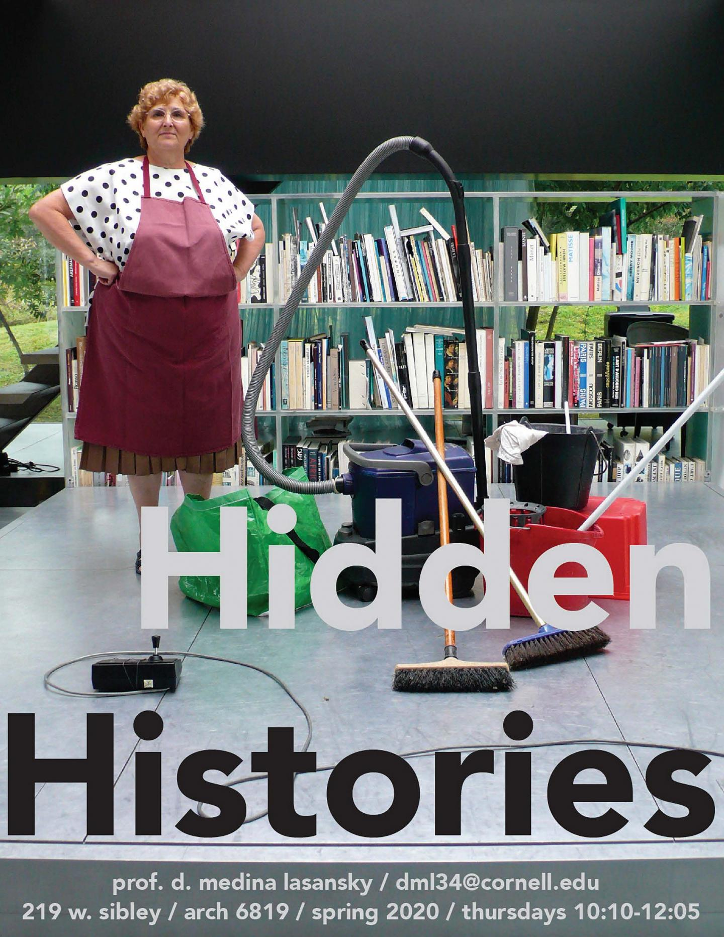 A woman wearing an apron stands with a vacuum cleaner, buckets, and cleaning supplies next to a bookcase filled with books.