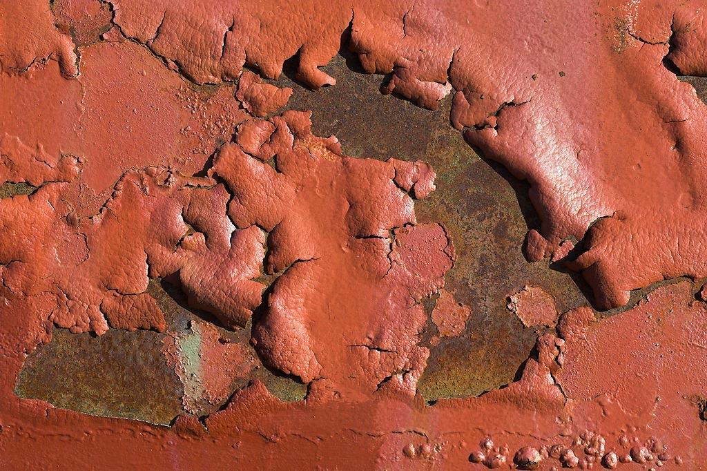 Red substance bubbled and peeling from a rusty metal surface