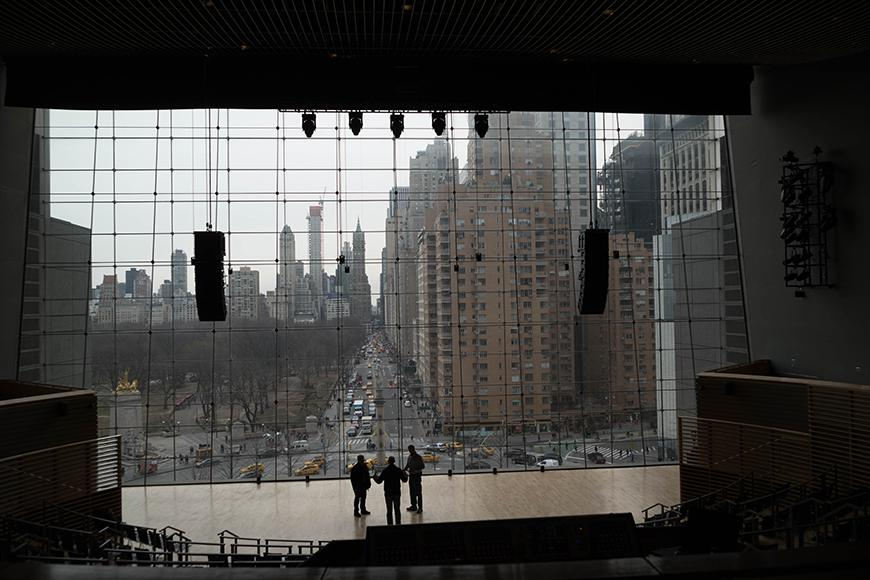 Three people on a stage in a glassed-in room overlooking a city