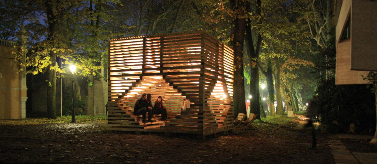 People sitting in a wooden sculpture/structure in outdoor setting at night