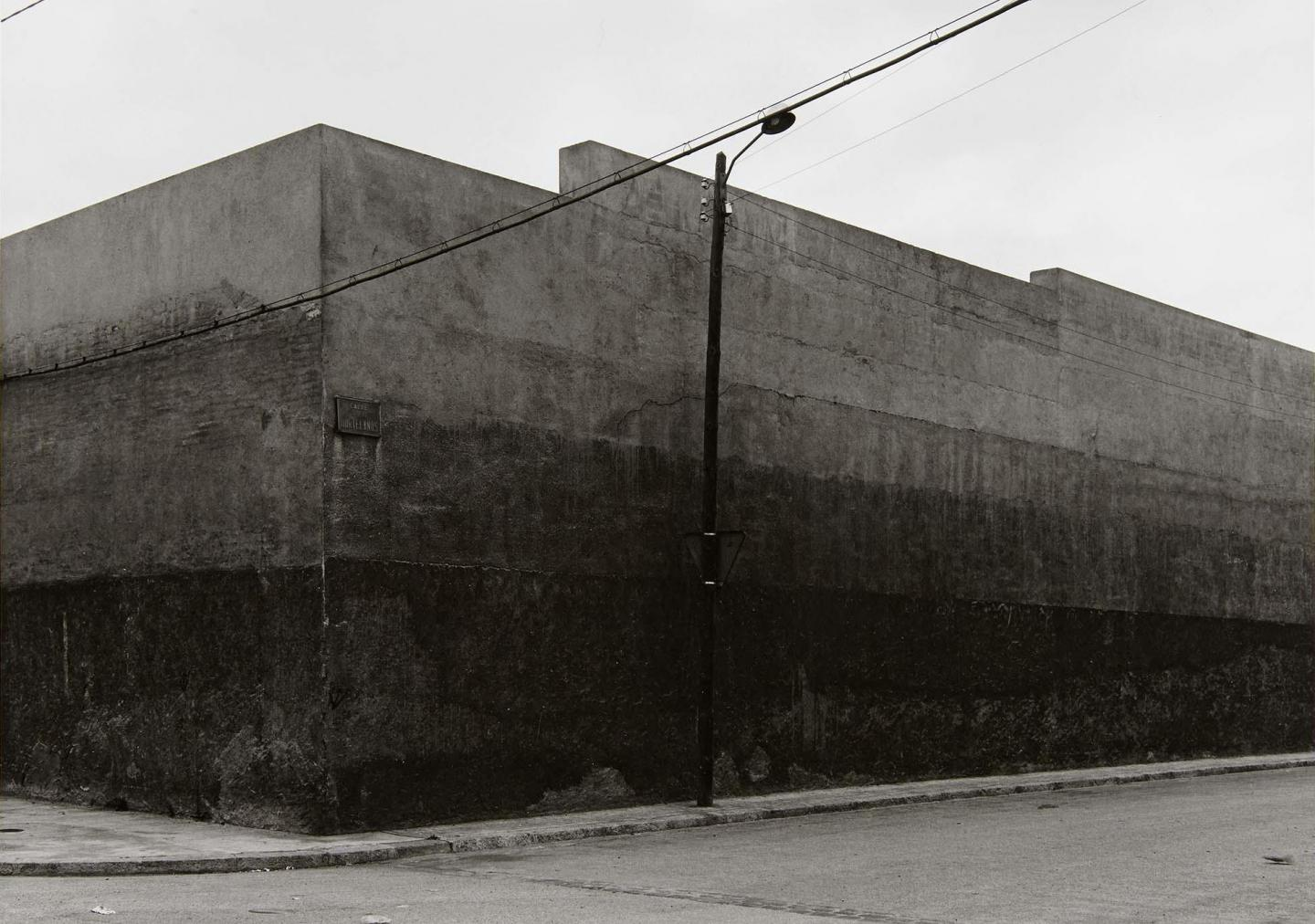 Block-shaped concrete building, utility pole, and wires.