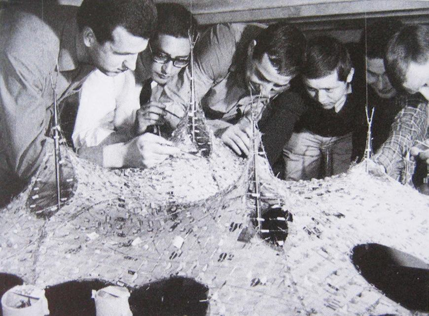 Black and white photo from the 70s of six men looking closely at a surface