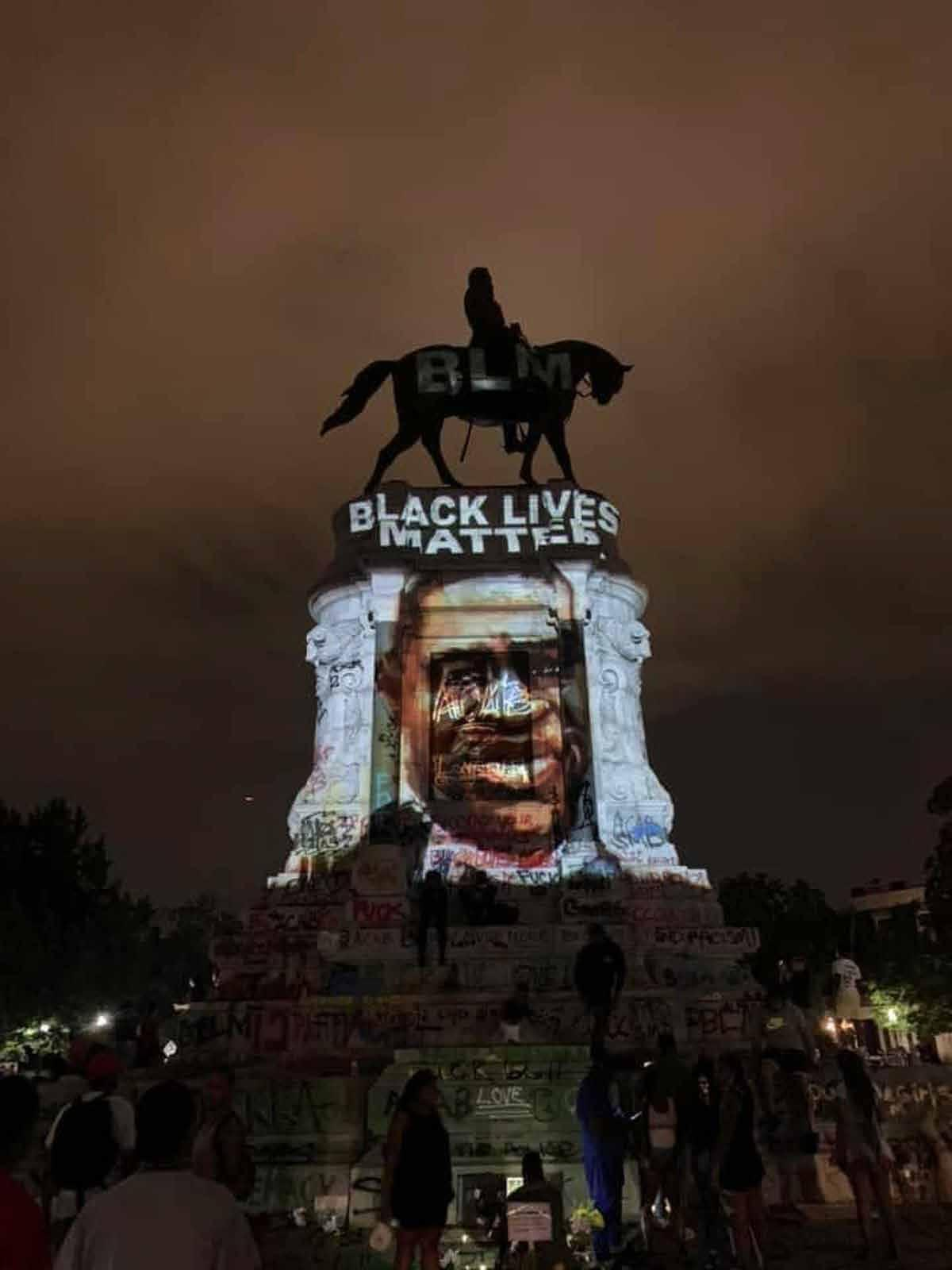 A person on horseback on a massive plinth and the face of a person projected on the plinth.