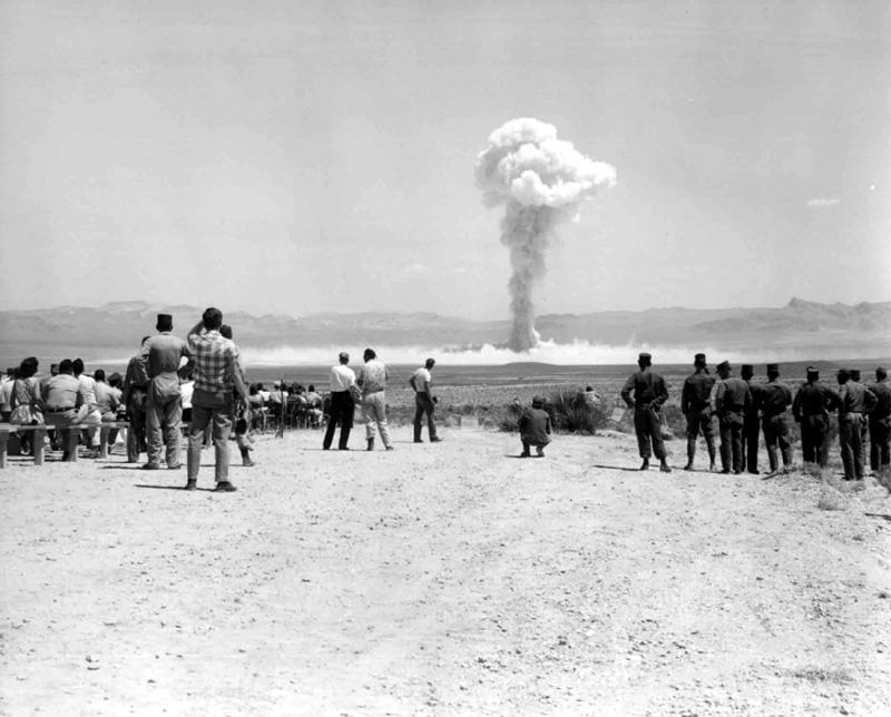 Crowd of people on a flat sandy area, a mushroom cloud rises in the sky.