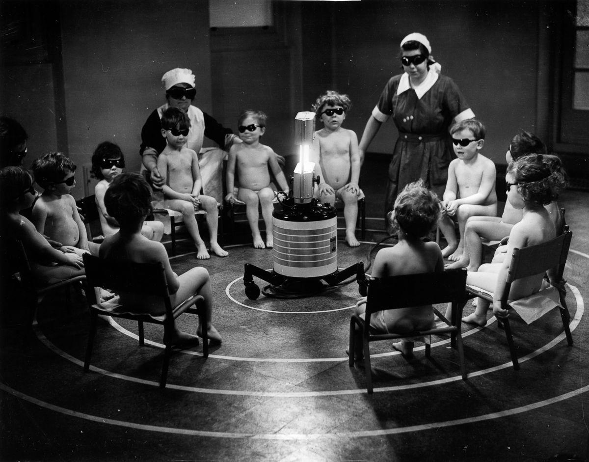 naked children and nurses wearing sun glasses gathered around a UV light