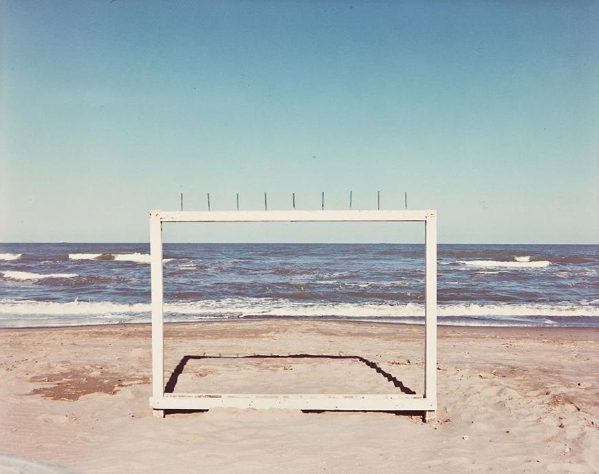 A wooden frame with spikes on top installed on a beach