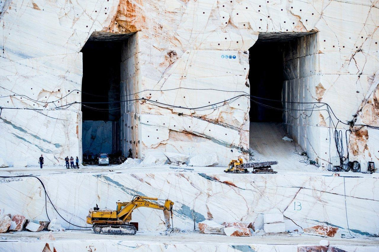 excavating machines and people in a Carrara marble mining site