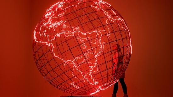 A person stands next to a large, translucent globe that glows red.