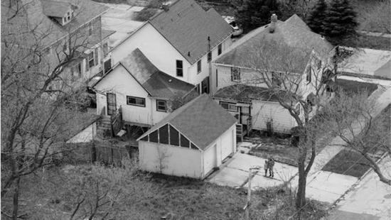 Rambling white house, sidewalk and street corner seen from above.