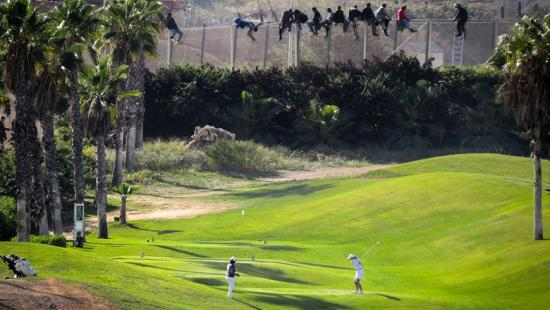 Golfers on a fairway with people on a fence in the background