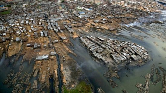 aerial view of a city and wharves at the edge of a body of water.