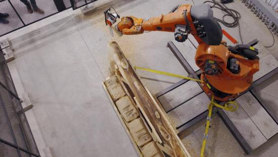 aerial view of an orange and black robot arm cutting a wooden log in a concrete-floored studio