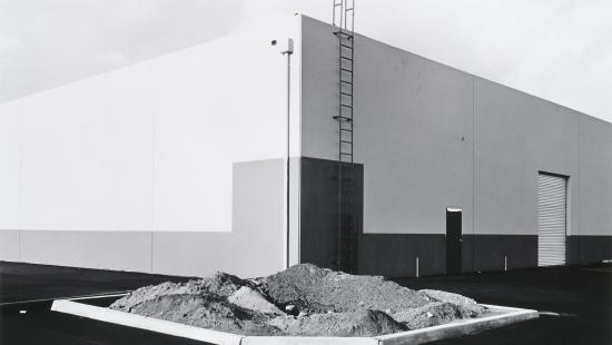 Oblong white building, a pile of dirt in front.