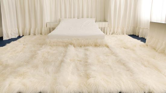 extravagant bedroom with a white fur bed cover