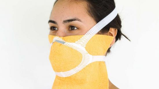 Person wearing a yellow face mask with white straps.