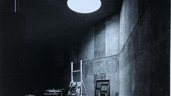 a round skylight sheds light on a table, an easel with a painting on it, and  empty frames leaning against the wall