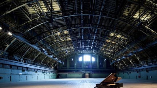a grand piano with the top opened on an empty stage in an empty curved-roof atrium