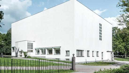 A white rectangular building with windows on the lower story set on green grass with a black metal fence