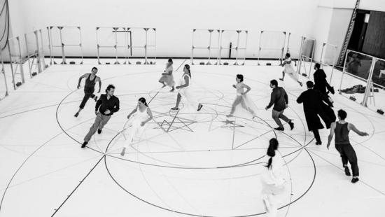 people running in circles on a white floor marked with circular diagrams
