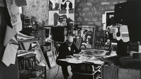 black and white image of a man seated at a desk in a studio with abstract art behind him