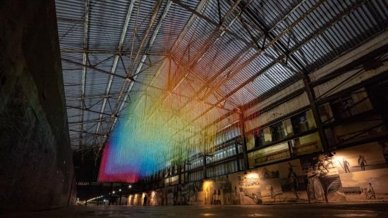 rainbow-clored patters projected in an atrium space under metal beams and a metal ceiling